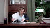 Young woman doing paperwork in the office sitting at her desk video