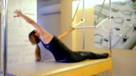 DOLLY: Young woman doing pilates exercise video