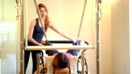 DOLLY: Young woman doing pilates exercise with instructor video