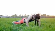 Young woman doing push-ups outdoors video