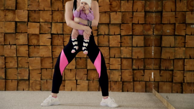 Young woman doing squats holding small baby in arms indoors video