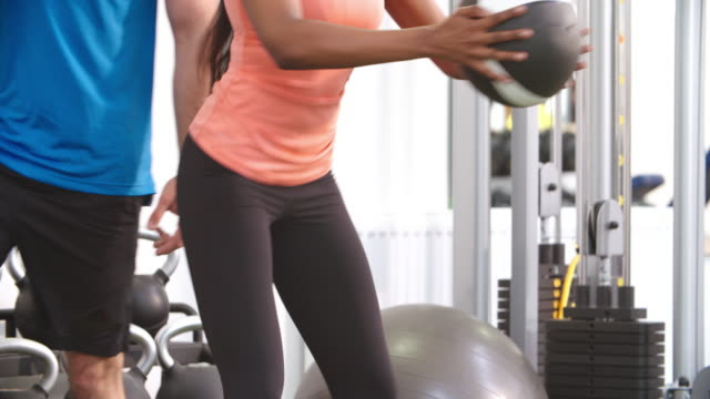 Young woman doing squats in a gym with a medicine ball video