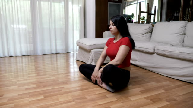 Young woman doing yoga breathing exercise and meditating in lotus position on the floor at home video
