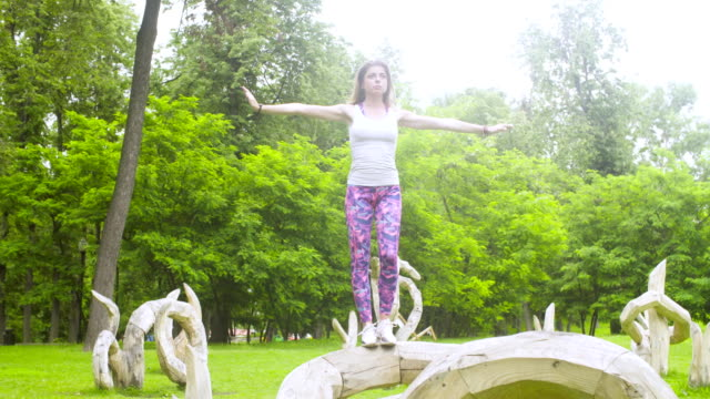 Young woman doing yoga exercises in the park video