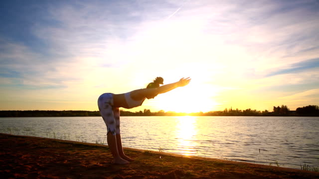 Young woman doing yoga exercises on the lake beach at sunset video