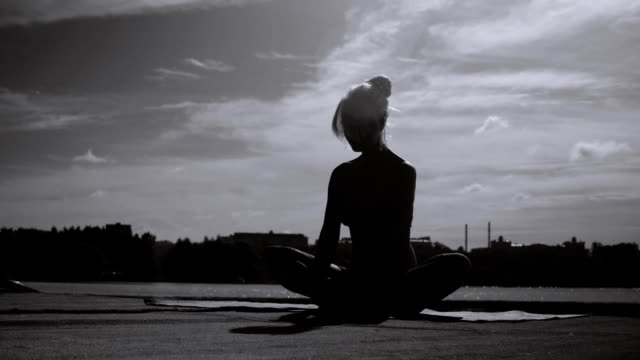 Young woman doing yoga exercises on the river bank video