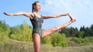 young woman doing yoga in a park outside video