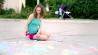 young woman draws a chalk on asphalt, close up video