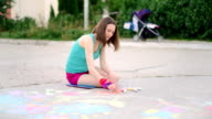 young woman draws a chalk on asphalt on playground video