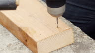 A young woman drills holes into wood for nailing in slow motion. video