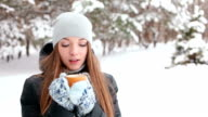 Young woman drink coffee in winter forest video