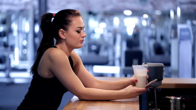 Young woman drinking a protein shake and looking at the phone video