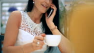 Young woman drinking coffee and talking on the mobile phone in cafe. video