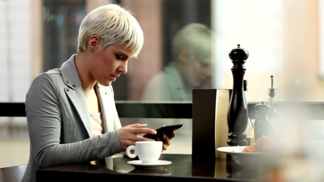 Young woman drinking coffee and using tablet video