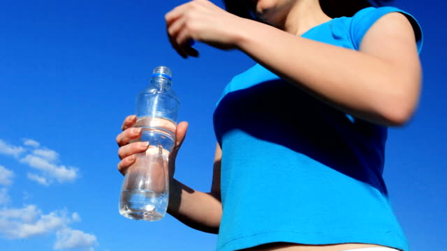 Young woman drinking fresh water from bottle. video
