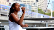 Young woman drinking outside video