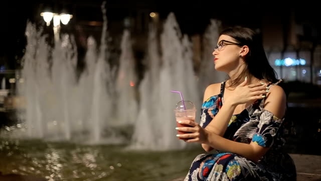 Young woman drinking strawberry smoothie on the street,night scene video