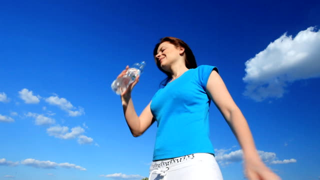 Young woman drinking water outside. video