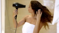 Young woman drying her long dark brown hair video