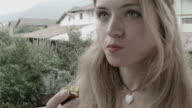 Young woman eating a plum on the veranda video