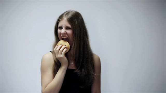 Young woman eating burger at gray background video