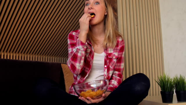 Young woman eating chips and watching tv on sofa video