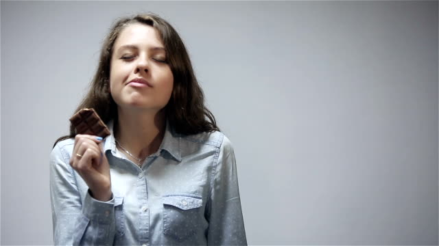 Young woman eating chocolate bar at gray background video