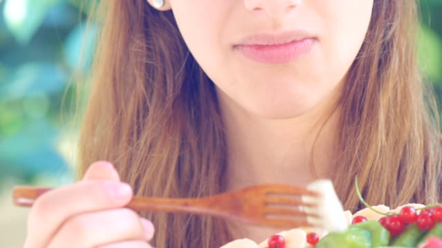 Young woman eating fruits salad. video