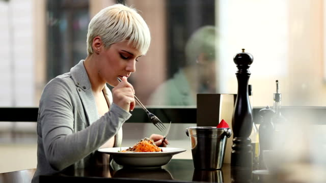 Young woman eating in a restaurant. video
