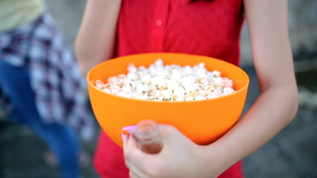 Young woman eating popcorn at a party video