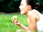 Young woman eats fresh apple outdoor video