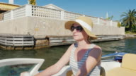 Young woman enjoying a holiday resort in Europe. Floating on a boat on the channel Empuriabrava, Spain video
