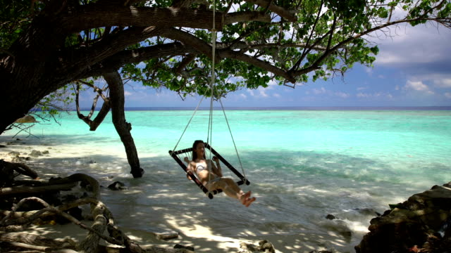 Young woman enjoying a rest in a hammock on the beach to the sound of the surf. video