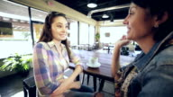 Young woman enjoying cup of coffee with mom at local diner video