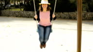 young woman enjoying swing in the park video