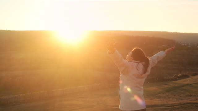 Young woman enjoying the freedom in nature at sunset. video