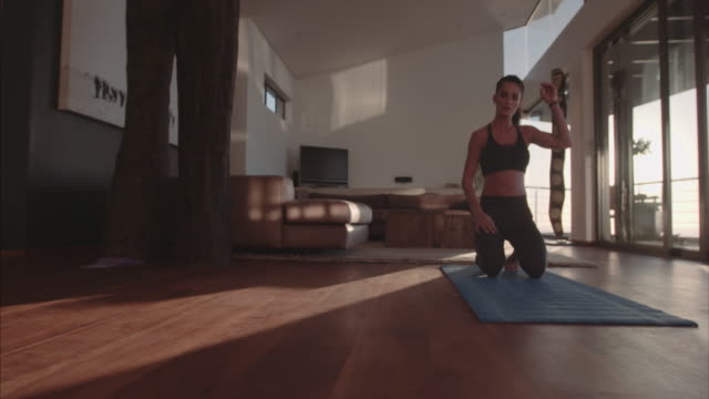 Young woman exercising at home doing push ups video