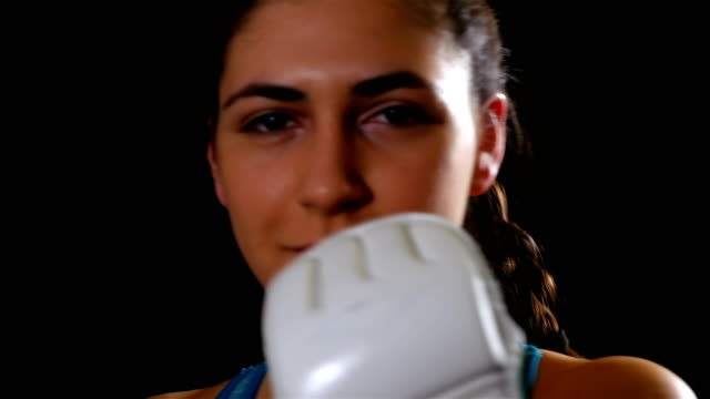 Young woman exercising boxing kicking training for self defense against the camera, sport fitness video