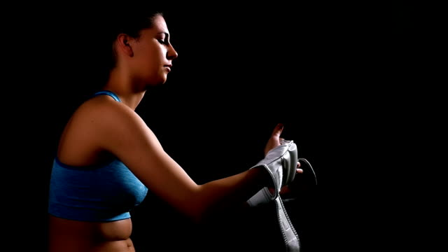 Young woman exercising boxing kicking training getting off gloves on black background, slow motion video