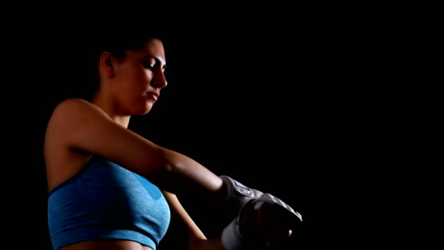Young woman exercising boxing kicking training putting on gloves on black background video
