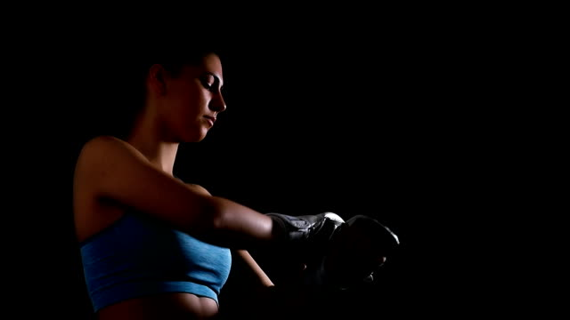 Young woman exercising boxing kicking training putting on gloves on black background, slow motion video