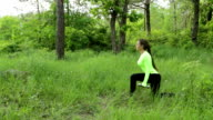 Young woman exercising, doing crouch with dumbbels in park video