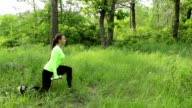 Young woman exercising doing crouch with dumbbels in park video