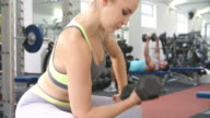 Young woman exercising with dumbbell at a gym video