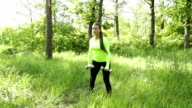 Young woman exercising with dumbbels in park near forest video
