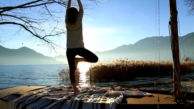 Young woman exercising yoga by the lake at sunset video