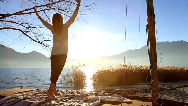 Young woman exercising yoga by the lake video