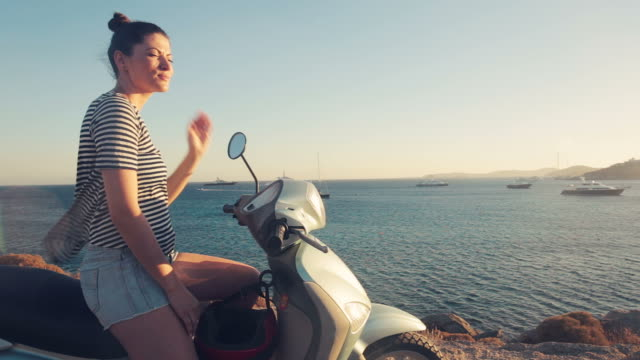 Young woman experiencing freedom at sunset on the motor scooter. video