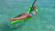 SLOW MOTION: Young woman falls off floating airbed raft mattress video