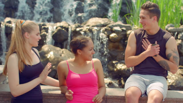 Young woman flirting with boy outdoor. Happy people talking near waterfall video